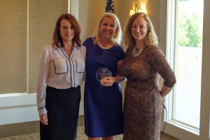 Kate Holcomb, APR, left, and Angela Daniels, right, present the award to Lori Campbell Baker